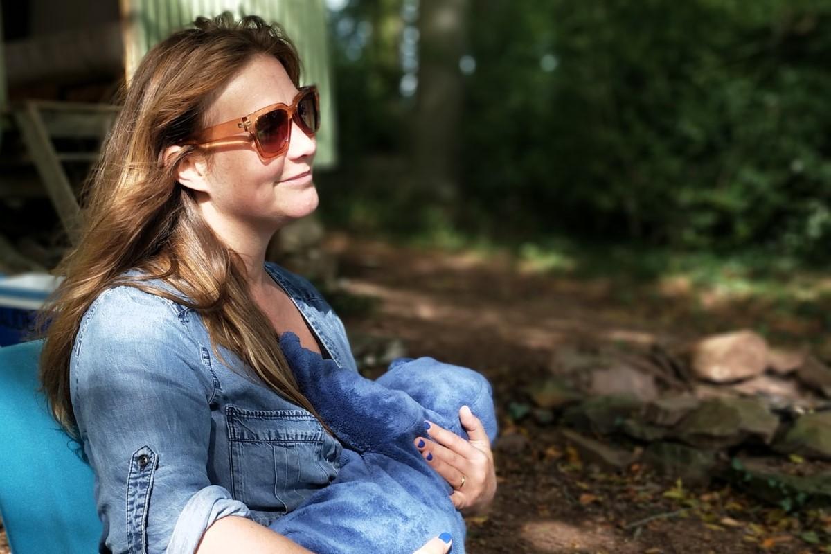 Kobieta karmiąca piersią na zewnątrz, wspiera odporność dziecka